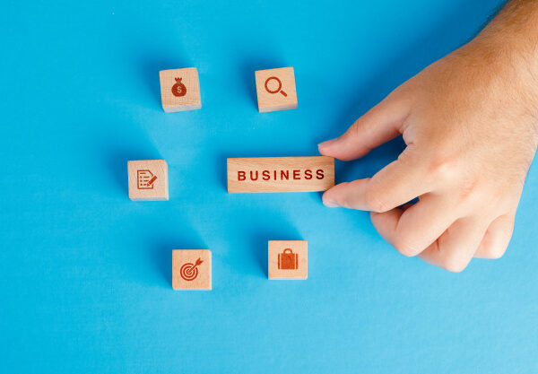 business-concept-with-icons-on-wooden-cubes-on-blue-table-flat-lay-hand-holding-wooden-block_176474-9353